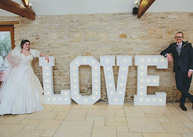 bride and groom light up giant love letters kingscote barn tetbury