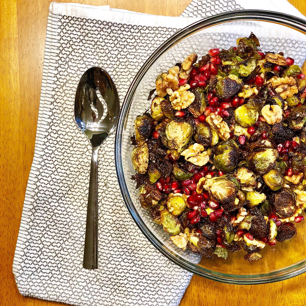 crispy roasted brussels sprouts with pomegranate arils and walnuts