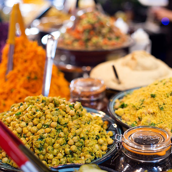 A wide selction of salads in bowls, with chickpeas and cous cous at the front.