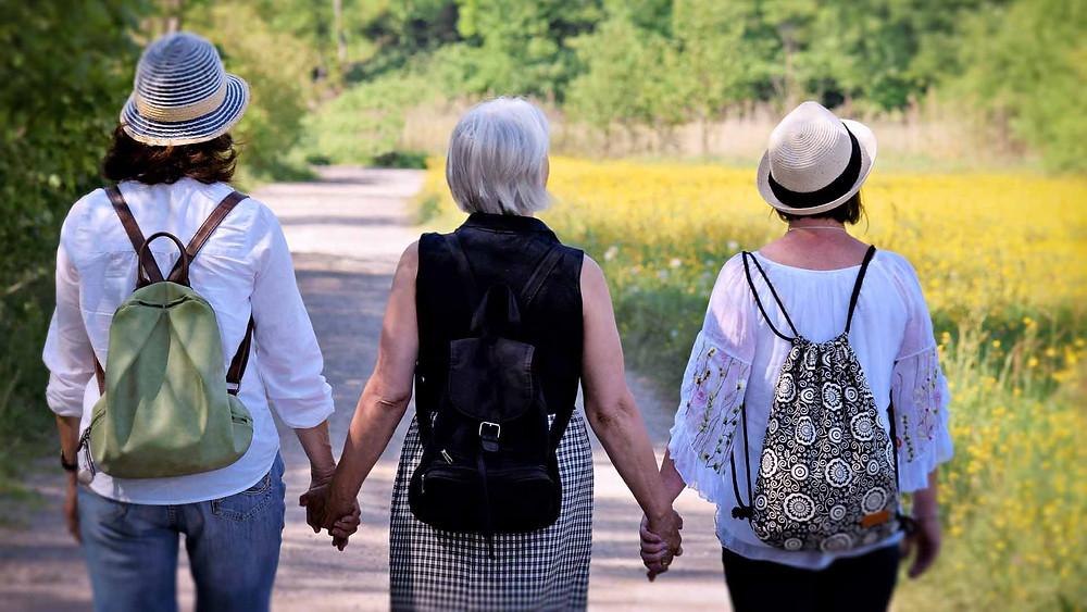 mulheres amigas de mãos dadas, juntas de costas, caminhando
