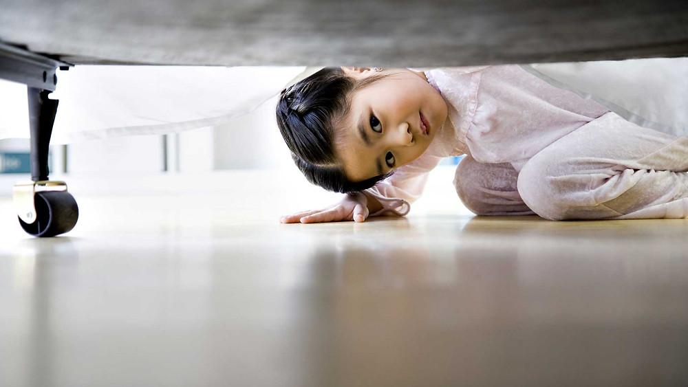 menina olhando em baixo da cama com medo do monstro medo de criança