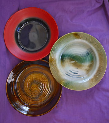 Three large wheel thrown platters with different sprayed glaze treatments