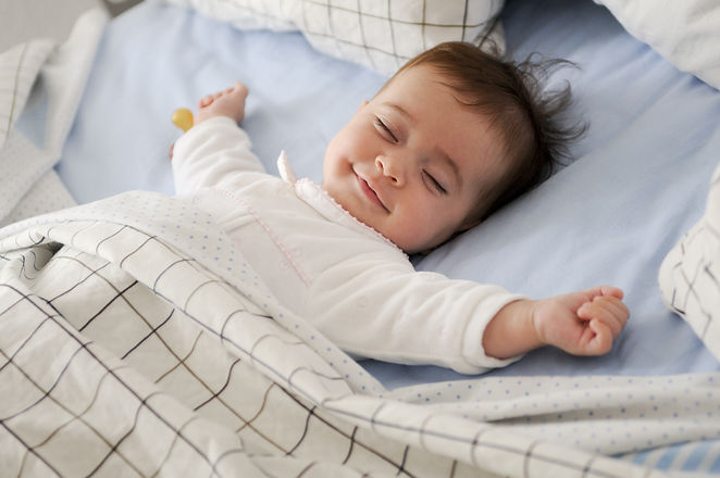 Smiling baby girl lying on a bed sleepin