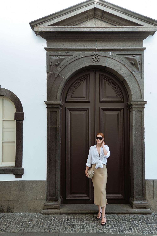 Suvelle de vestido slip bege e camisa branca em frente a porta antiga de igreja castanha