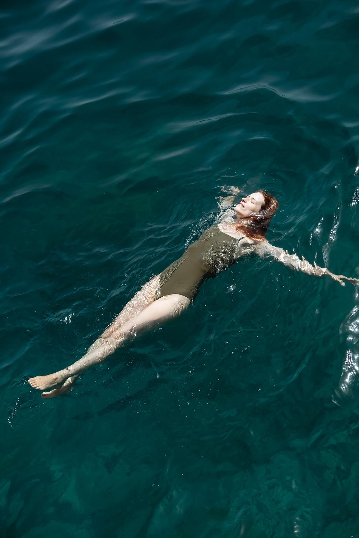 Suvelle com fato de banho verde a flutuar na água verde do mar na ilha da Madeira