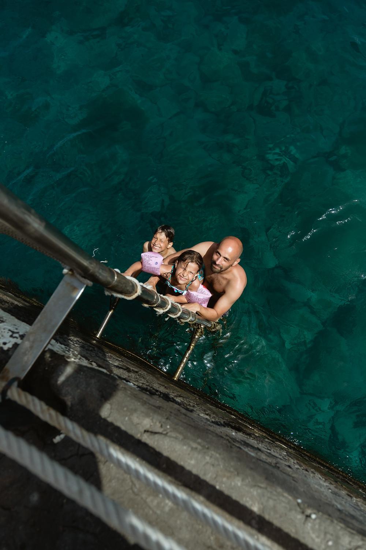 Pai e filhos na água verde da ilha da Madeira