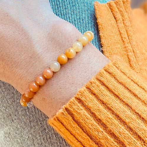 Armband van gele Jadekralen en oranje aventurien kralen getoond op arm