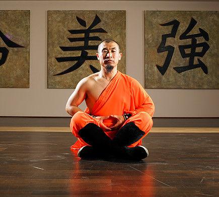 Master Xingbo Liu in traditional Shaolin uniform meditating