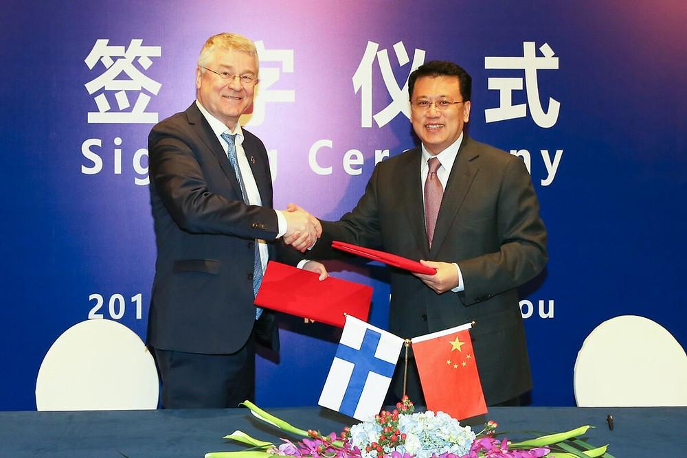 Markku Markkula and Yuan Jiajun exchange signed agreements