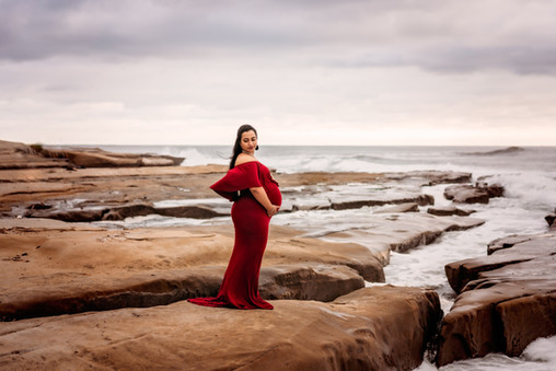 Mother in red dress on the beach