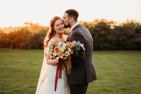 Bride with flowers and groom kissing bride