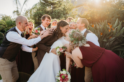 Bride and groom kissing in front of people