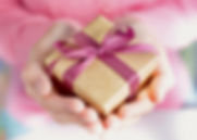In front of a soft focus background, feminine hands cup a gold gift box with a satin pink ribbon.