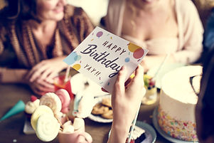 "A feminine hand holds a birthday card which reads ""Happy Birthday YAY!!!"" in front of a soft focus background of party food and a birthday cake on a table and two women sit smiling on the other side of the table."