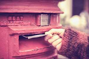 A feminine hand is pushing a letter into a traditional red post box, with a soft focus background.