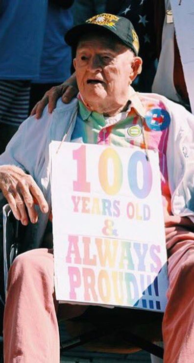 "An elderly man wearing a cap and rainbow shirt sits in a wheelchair smiling, with a light placard hanging around his neck which reads ""100 years old & always proud!!!"""