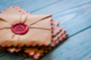 A pile of old fashioned brown envelopes with blue and red dashed edges a loosely piled on a blue wood background. There is a vintage red wax seal on the top envelope.
