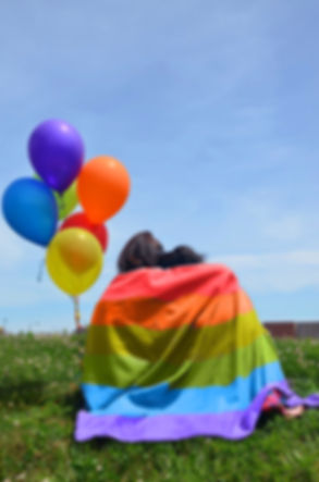 Two long haired brunettes sit in a field of greenery, their backs to the camera witha pride flag wrapped around them both and rainbow coloured balloons tied together next to them.