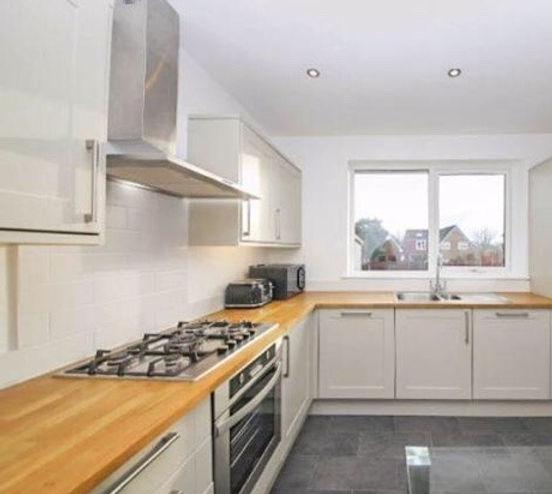 Modern white kitchen, slate floor, beech work surfaces