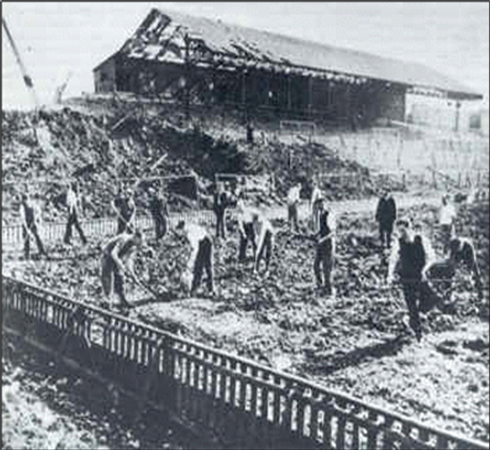 Groundsmen digging up football pitch, ci