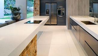 Kitchen with minimalist white work surfaces and american style fridge freezer
