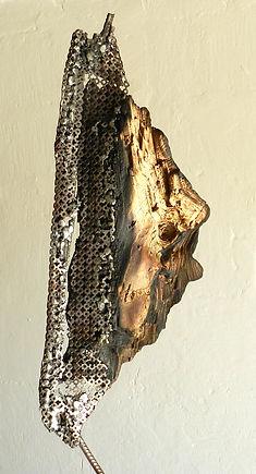 Sculpture bois glané et métal perforé. Le bois calcine et le métal chauffe.