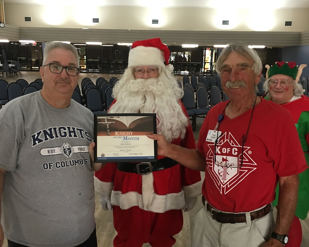 Brother Hebert receives certificate with Santa and an Elf looking on