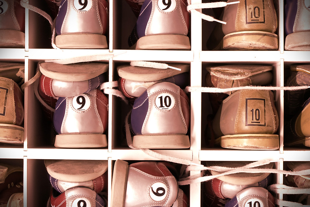 bowling shoes of different sizes in a rack