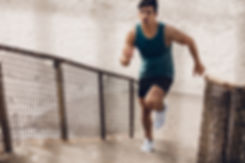 Fitness man running up the steps on beac