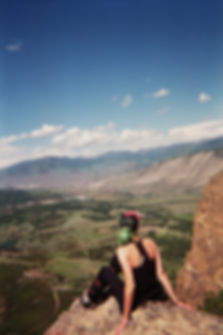 Grainy film photo of a girl sitting on a rock high above a mountainous valley