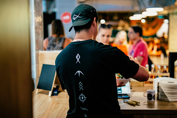 The co-founder of Ika Bowl serving a bowl to a customer