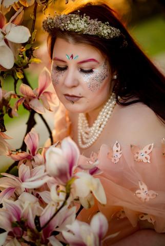 frau-kreatives makeup-blumenkranz-magnolie-blüte-schmetterling-perlenkette