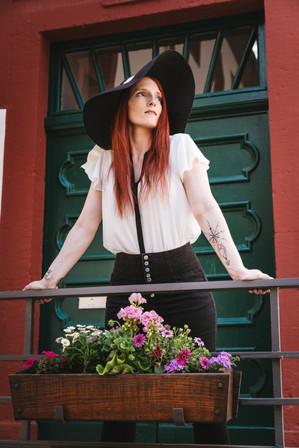 frau-schlank-sommerhut-geländer-weiße bluse-fernweh-portrait