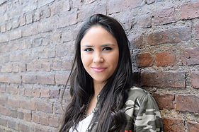 Hispanic Woman Against A Brick Wall..jpg