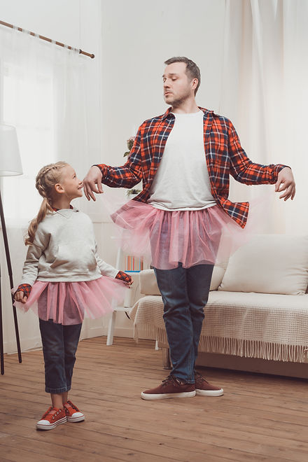 happy father and daughter in pink skirts