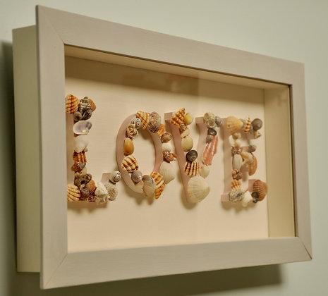 Handmade seashell letters in wooden frame