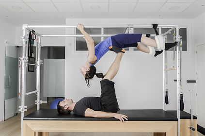 Man and woman doing exercise pilates wit
