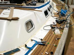 A new vacuum-glued teak deck is being laid