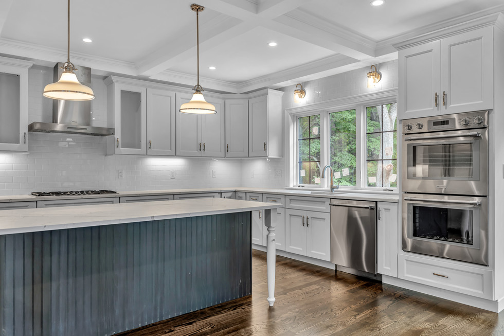 Dark inky-blue island contrasts with the white kitchen and countertops