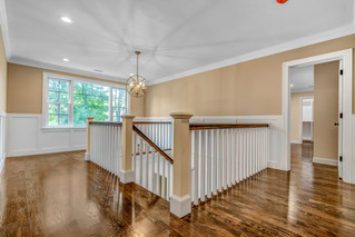 White and wood stair railing with geometric light fixture