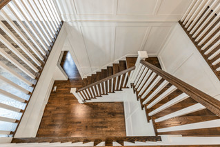 White and wood staircase paired with white walls millwork and hardwood flooring