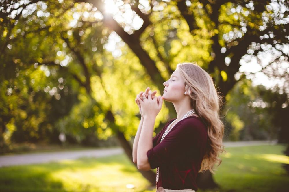 Mulher em oração na natureza | Foto de Ben White no Unsplash