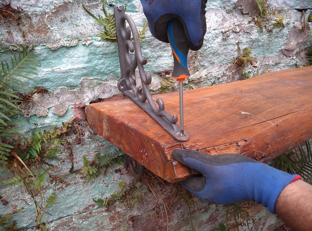 Construindo a Horta fixando a tábua nas mãos-francesas da parede | Foto Robriane Lara ©