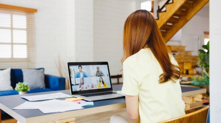 Mãe em reunião online na sala de estar da sua casa, local iluminado e espaçoso | Foto Freepik