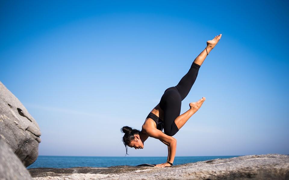 Mulher em postura de yoga em frente ao oceano | Foto Pixabay