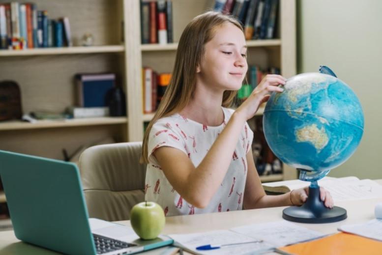 Estudante sentada confortavelmente com notebook na mesa de estudos, globo terrestre, lanche maça | Foto Freepik