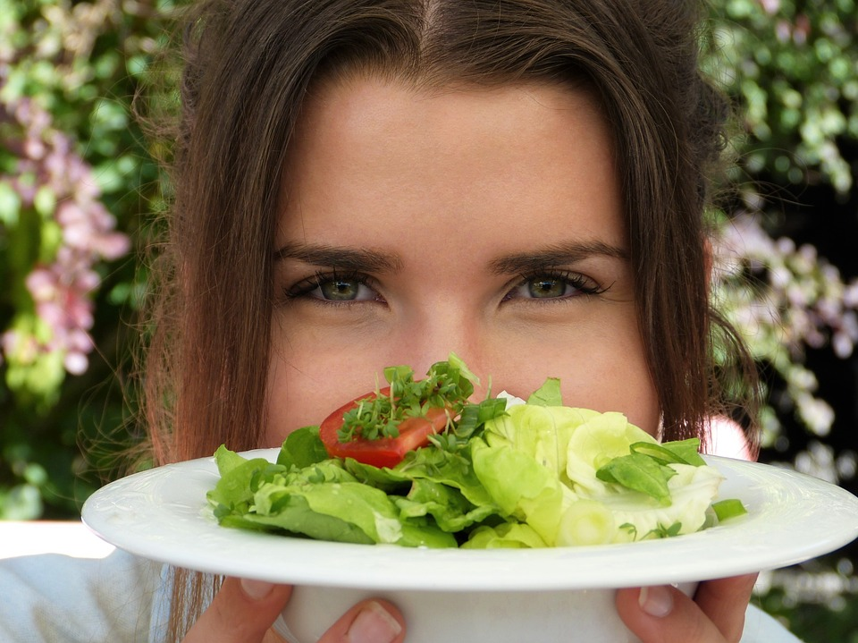 Jovem mostrando um prato com saladas verdes | Foto Pixabay