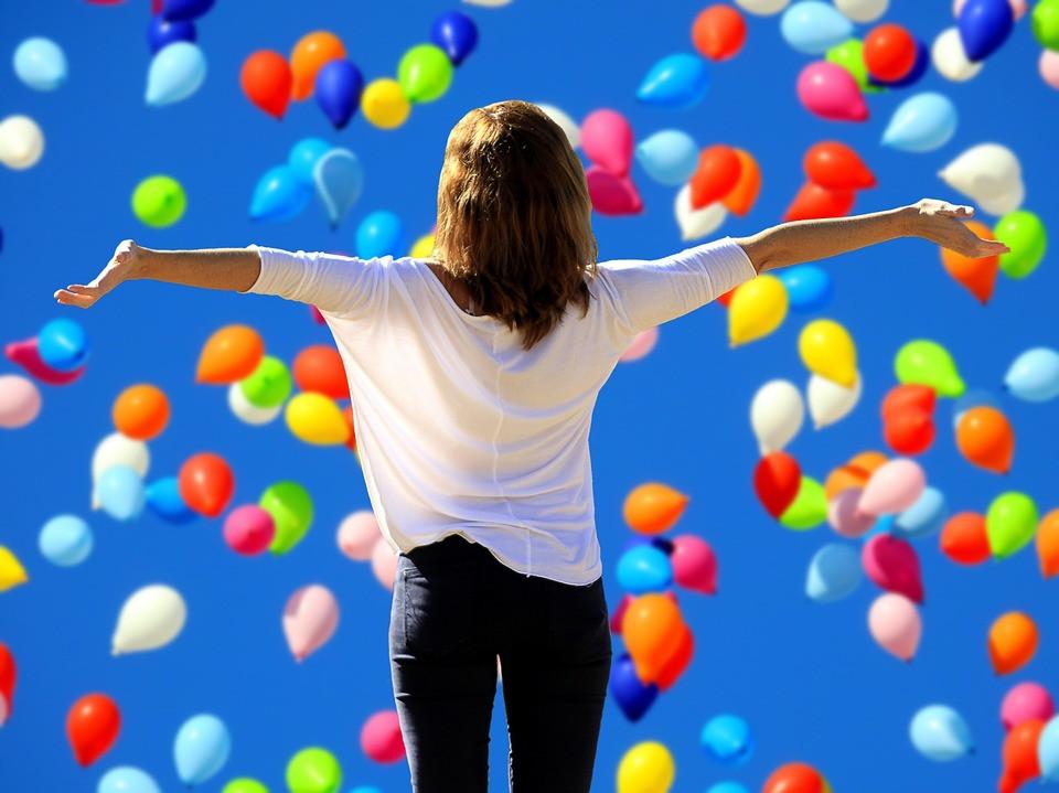 Mulher de braços abertos em gratidão e balões coloridos | Foto Pixabay