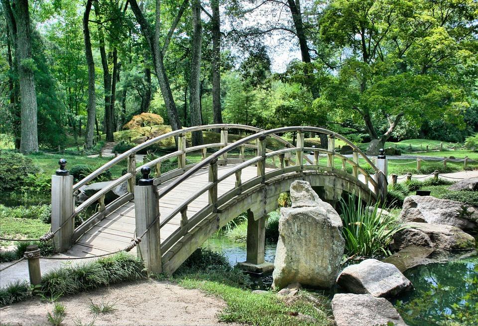 Cenário ajardinado com árvores, córrego, ponte e pedras de rio | Foto Pixabay