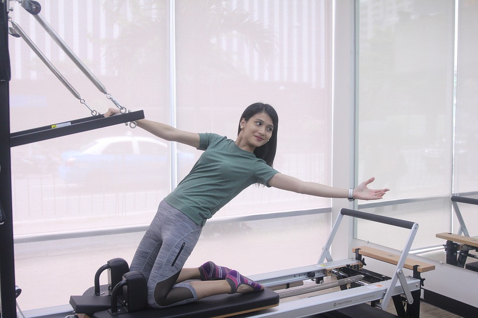 Moça fazendo Pilates com auxílio de aparelho com molas | Foto Pixabay